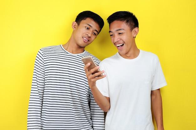 스마트폰 보고 웃는 행복한 두 캐주얼 남자의 초상화. 노란색 배경 위에 휴대폰을 보고 웃고 있는 잘생긴 두 젊은이의 초상화