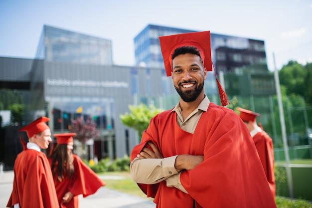 カメラ屋外卒業コンセプトを見て帽子とガウンと幸せな大学生の肖像画