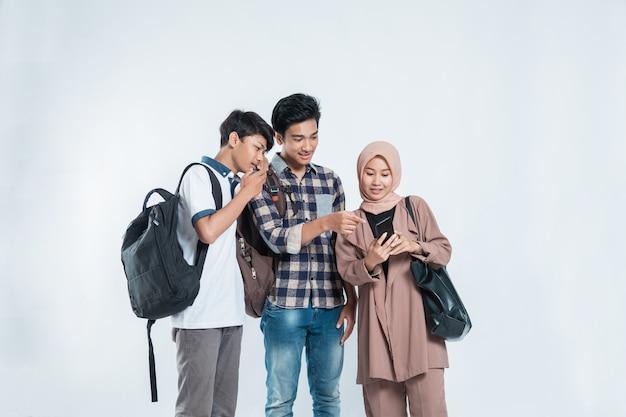 Портрет счастливой университетской молодежи, несущей сумки и обсуждения, глядя на сотовые телефоны, изолированные на белом фоне