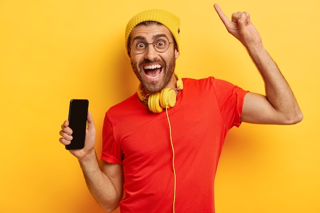 행복하지 않은 남자의 초상화는 빈 화면이있는 휴대 전화를 들고 위의 검지 손가락으로 팔과 포인트를 올리고 기쁜 표정을 지으며 노란색 모자와 빨간 티셔츠를 입고 헤드폰을 사용합니다.