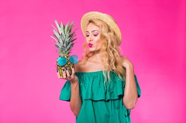 Портрет счастливой женщины и ананаса на розовом фоне. лето, диета и здоровый образ жизни