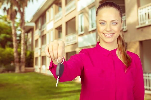 車のキーを保持している幸せな女性の肖像画