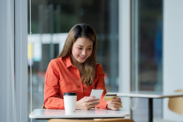 モールのクリエイティブなオフィスやカフェでクレジットカードと笑顔でスマートフォンを持っている幸せな女性の肖像画