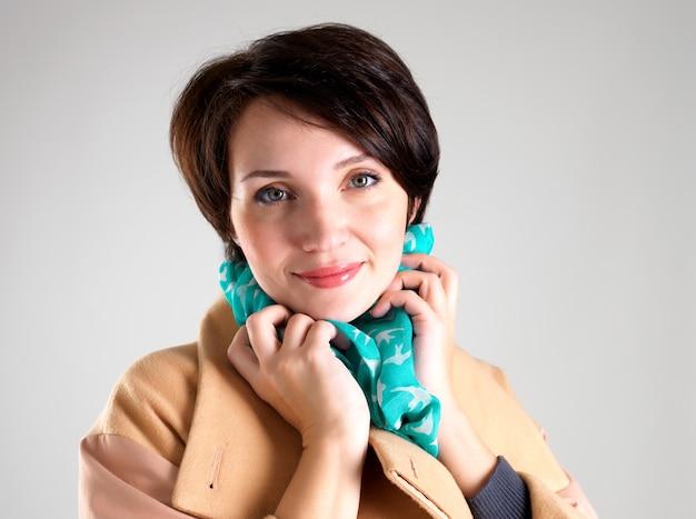 Портрет счастливой женщины в бежевом осеннем пальто с зеленым шарфом на сером фоне