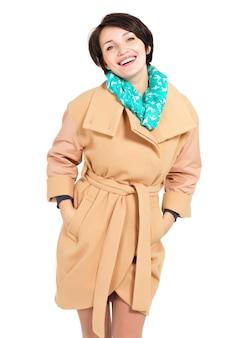 Портрет счастливой женщины в бежевом пальто с зеленым шарфом, стоящим изолированным на белом