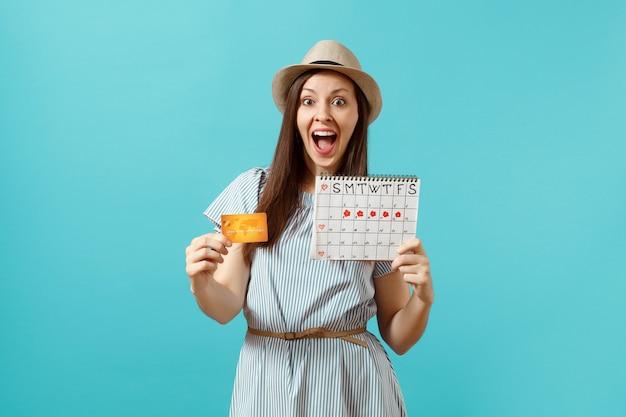 파란 드레스를 입은 행복한 여성의 초상화, 신용카드를 들고 있는 모자, 기간 달력, 유행하는 파란색 배경에 격리된 월경일 확인. 의료 의료 부인과 개념입니다. 공간을 복사합니다.