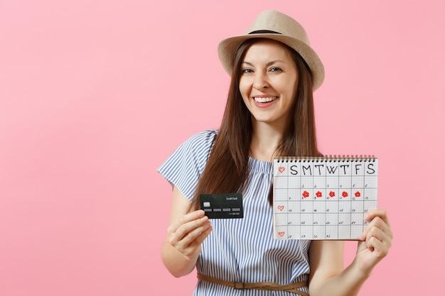 파란 드레스를 입은 행복한 여성의 초상화, 신용카드를 들고 있는 모자, 생리 달력, 유행하는 분홍색 배경에 격리된 월경일 확인. 의료 의료 부인과 개념입니다. 공간을 복사합니다.