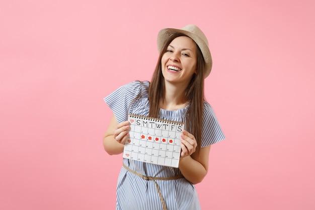 파란 드레스를 입은 행복한 여성의 초상화, 밝은 분홍색 배경에 격리된 월경일을 확인하기 위한 기간 달력을 들고 있는 모자. 의료, 건강 관리, 부인과 개념입니다. 공간을 복사합니다.