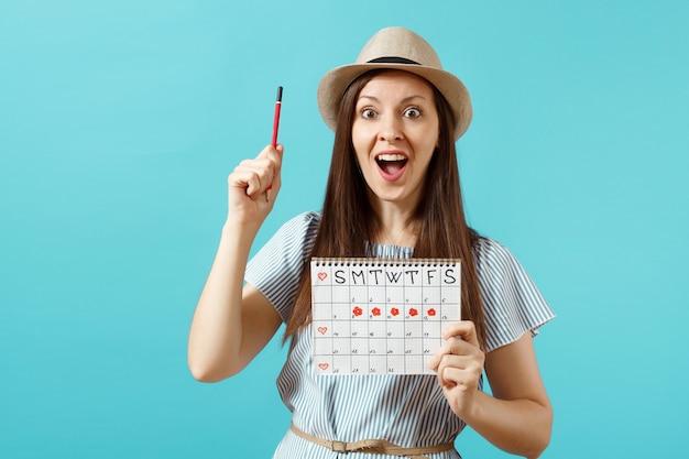 파란 드레스를 입은 행복한 여성의 초상화, 빨간 연필을 든 모자, 파란 배경에 격리된 월경일을 확인하기 위한 여성 기간 달력. 의료 의료, 부인과 개념입니다. 복사 공간