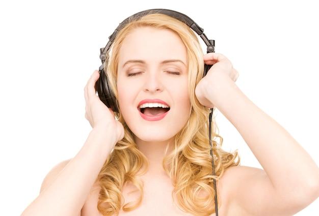 흰 벽에 헤드폰에 행복 한 여자의 초상화