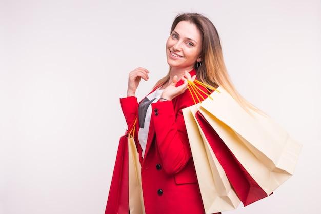 복사 공간이 있는 쇼핑백을 들고 빨간 양복을 입은 행복한 여성의 초상화.