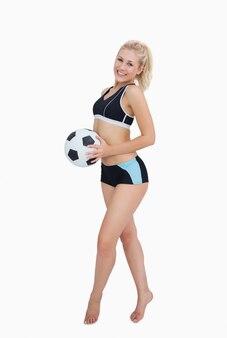축구를 들고 운동복에 행복 한 여자의 초상화