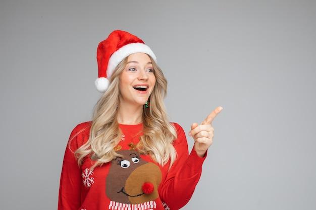 스웨터와 cristmas 모자를 쓴 행복한 여성의 초상화는 무언가에 기뻐합니다