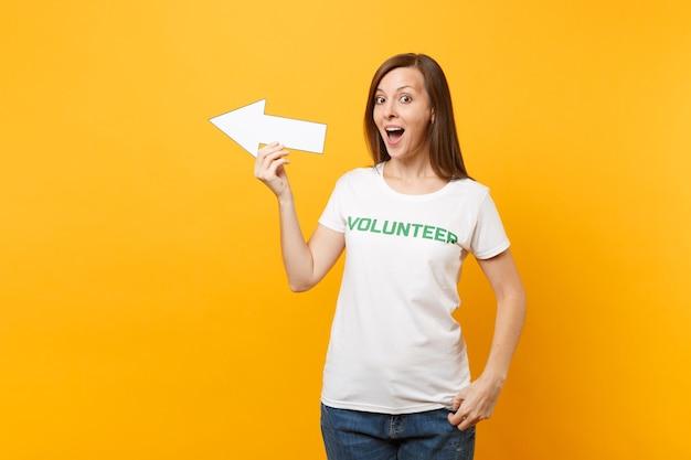 흰색 티셔츠를 입은 행복한 여성의 초상화는 녹색 제목 자원 봉사자가 노란색 배경에 격리된 옆을 가리키는 화살표를 잡고 있습니다. 자발적인 무료 지원 도움, 자선 은혜 작업 개념.