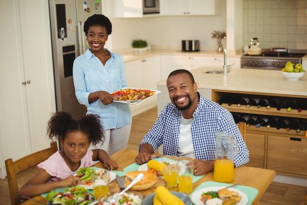 家族に料理を提供する幸せな女の肖像