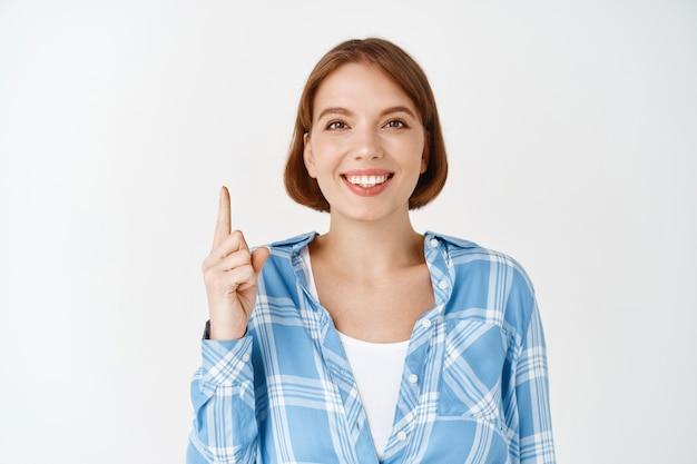 笑顔、人差し指、方向を示す幸せな女性の肖像画。白い壁に特別な取引を発表する少女