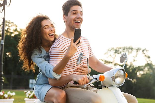 그녀의 남자 친구와 함께 도시 거리를 통해 오토바이를 타고있는 동안 스마트 폰에서 사진을 찍는 행복한 여자의 초상화