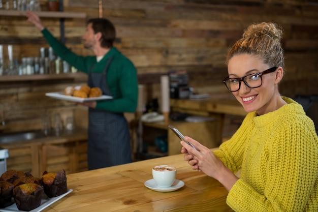 바리 스타가 커피 숍에서 백그라운드에서 작업하는 동안 휴대 전화를 사용하여 행복한 여자의 초상화