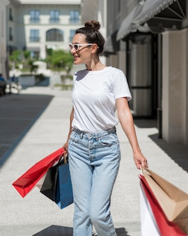 買い物袋で歩いて幸せな女の肖像