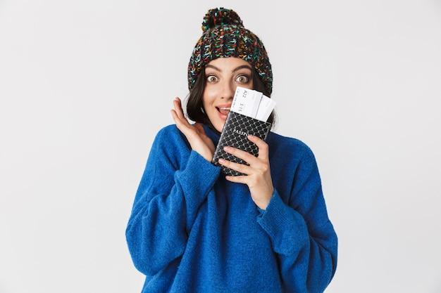 Портрет счастливой женщины в зимней шапке, держащей паспорт и проездные билеты стоя, изолированную на белом