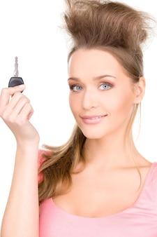 Портрет счастливой женщины с ключом от машины над белой стеной