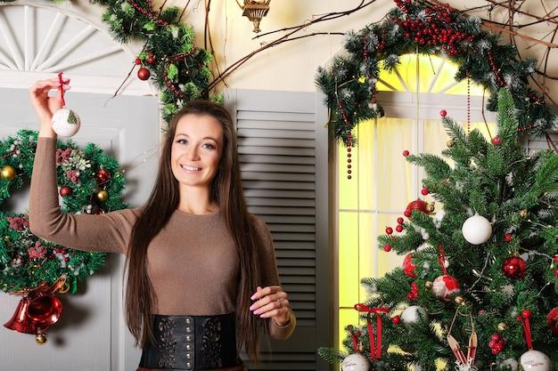 お祝いの木の近くで手にクリスマスの装飾と幸せな女性の肖像画