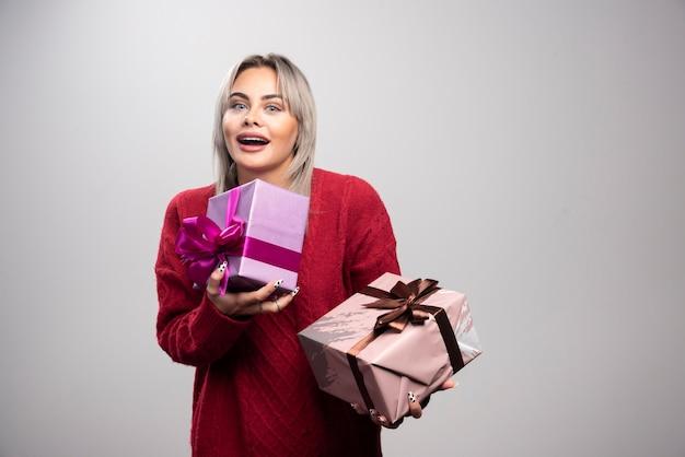 회색 배경에 선물 상자가 서 있는 행복한 여성의 초상화.