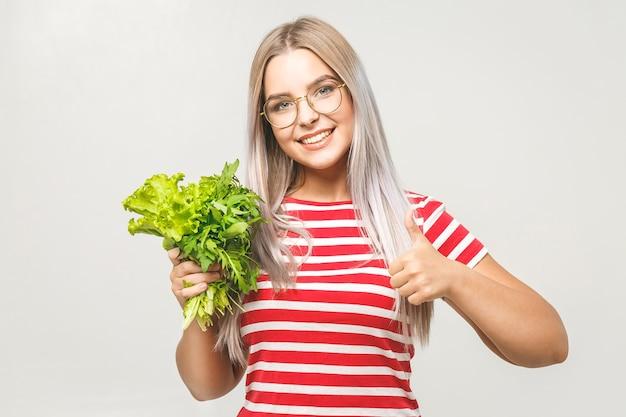 白い背景の上に分離されたレタスと幸せな女性の肖像画。食品野菜健康コンセプト。いいぞ。