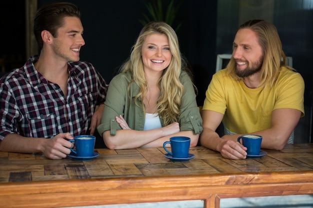 Портрет счастливой женщины с друзьями-мужчинами за столом в кафе