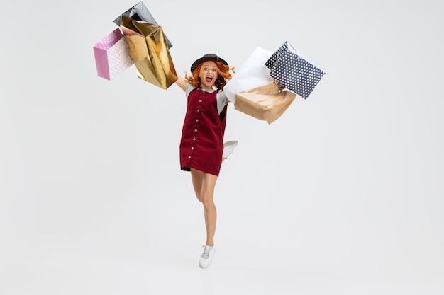 흰색 스튜디오 배경에서 격리된 쇼핑 후 많은 패키지를 가진 행복한 여성의 초상화