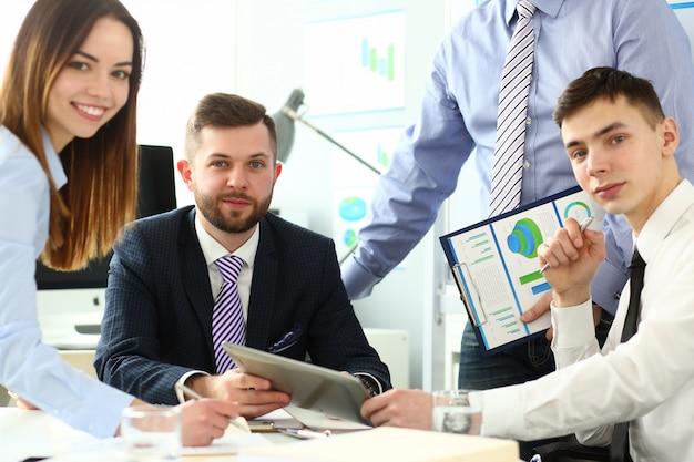 Портрет счастливых работников смотря с радостью и большой концентрацией. молодой менеджер, держа бумажный планшет и обсуждая документ с умными коллегами
