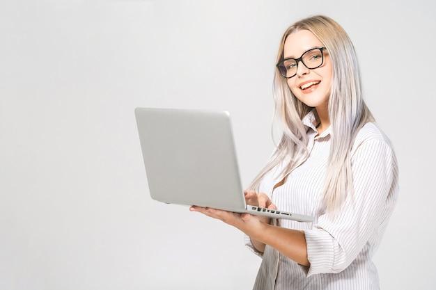白い背景で隔離のラップトップと立っている幸せなすごい若い美しい笑顔の女性の肖像画。テキスト用のスペース。
