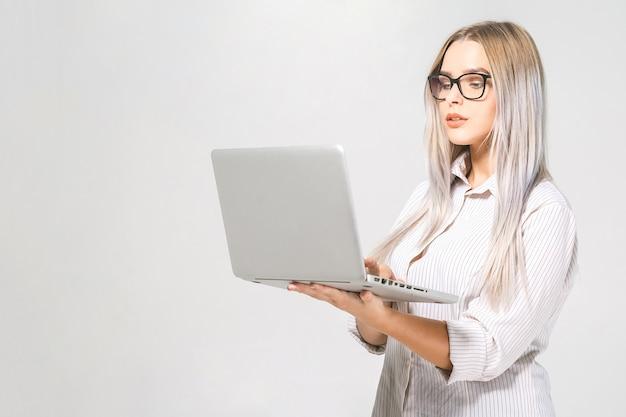 ノートパソコンで立っている幸せなすごい若い美しい笑顔の女性の肖像画