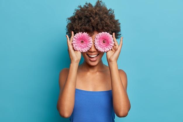 행복 한 젊은 아프리카 계 미국인 여자의 초상화는 장밋빛 gerberas로 눈을 덮고, 재미 있고, 좋아하는 꽃을 보유하고, 파란색 탑을 입은 이빨 미소를 가지고, 여가 시간을 즐깁니다.