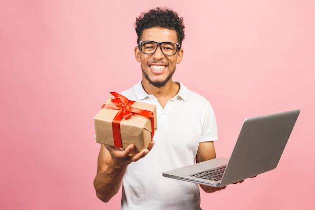 Портрет счастливого молодого афроамериканца, использующего портативный компьютер, подарочную коробку и проверку