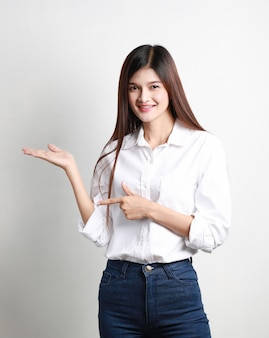 흰 벽에 고립 된 포즈 행복 젊은 아시아 사업가의 초상화, 아름다운 웃는 태국 소녀 가리키는, 비즈니스 개념.