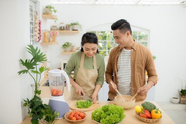 집에서 부엌에서 함께 요리하는 행복한 젊은 아시아 부부의 초상화.