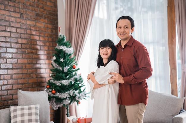 幸せな若いアジアのカップルの肖像画は、自宅でクリスマスの日に踊って一緒に時間を楽しんでいます