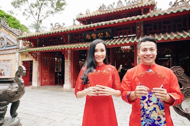仏教寺院に立って、赤い幸運なお金の封筒を示す伝統的なドレスを着た幸せな若いアジアのカップルの肖像画