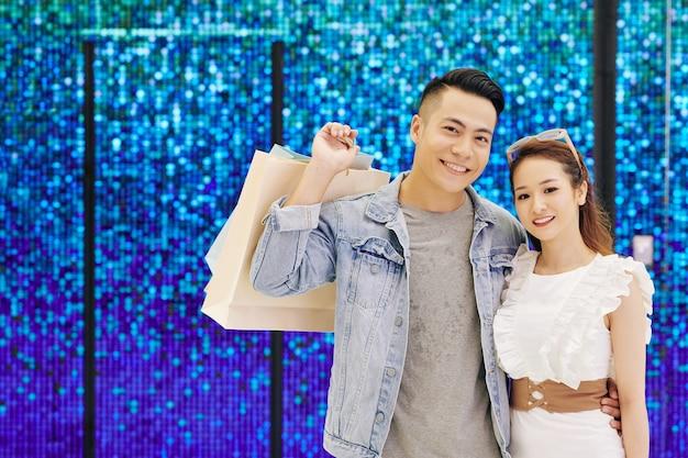 ショッピングバッグと青い輝く壁に立って、正面に笑みを浮かべて幸せな若いアジアのカップルの肖像画