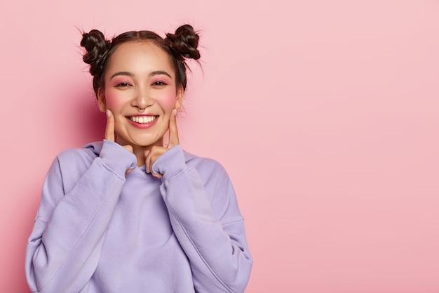 행복 한 젊은 아시아 여자의 초상화 실내 서, 검지 손가락으로 뺨을 만지고, 캐주얼 보라색 후드를 입고 얼굴에 즐거운 미소를 가지고, 핀업 메이크업을 착용