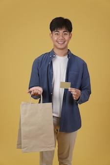 행복 한 젊은 아시아 남자의 초상화 부담없이 쇼핑 가방과 고립 된 신용 카드를 들고 옷을 입고