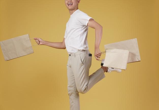 행복 한 젊은 아시아 남자의 초상화는 부담없이 고립 된 쇼핑백을 들고 옷을 입고