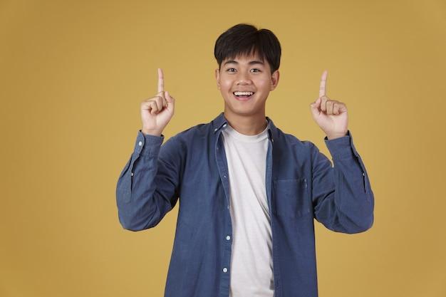 Портрет счастливого молодого азиатского человека одетого небрежно указывая пальцем вверх на copyspace