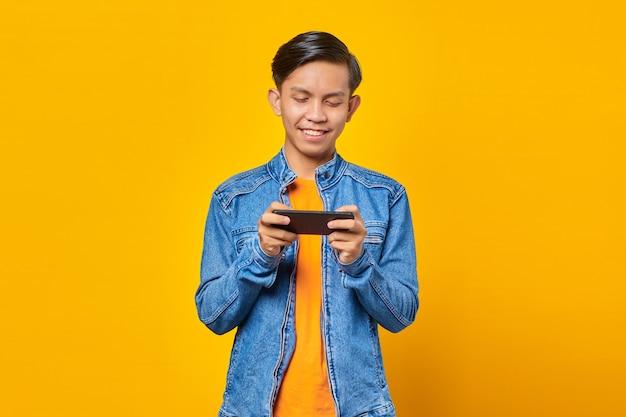 휴대폰으로 비디오 게임을 하는 행복한 젊은 아시아 남자의 초상화