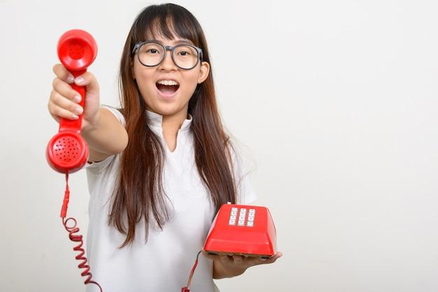 Портрет счастливой молодой азиатской женщины ботаника, дающей старый телефон
