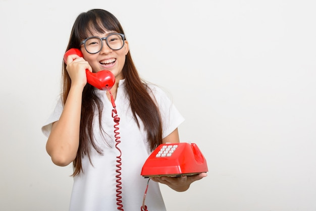 Портрет счастливой молодой азиатской женщины ботаника, использующей старый телефон