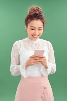 Портрет счастливой молодой азиатской женщины, держащей смартфон на зеленом фоне.