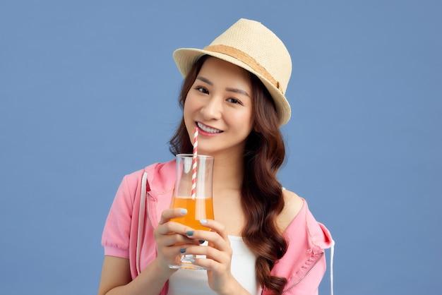 파란색 배경 위에 밀짚모자를 쓰고 과일 주스를 마시는 행복한 젊은 아시아 여성의 초상화.