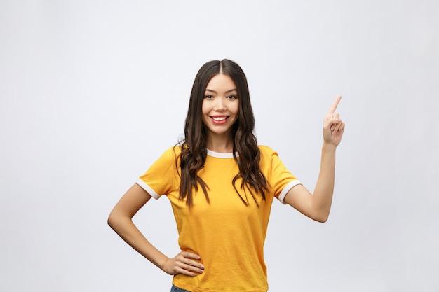 손가락으로 행복 한 젊은 아시아 여자의 초상화를 가리킨